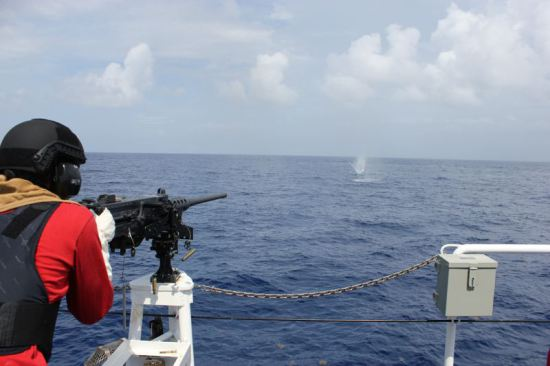 A crew member of the Coast Guard's second Fast Response Cutter, Richard Etheridge, fires a.50 caliber machine gun July 17 during the cutter's first live fire exercise. Richard Etheridge will be commissioned on August 3 in Port Everglades, Fla. and homeported in Miami alongside the first FRC, Coast Guard Cutter Bernard C. Webber. USCG photo by Lt. James Ellsworth.